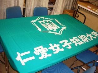 テーブルに広げた仁愛女子短期大学旗の写真