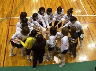 円陣を組む本学バレーボール選手たちの写真